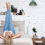 Expressing happiness. Young blond-haired woman lying on bed and holding her legs up.