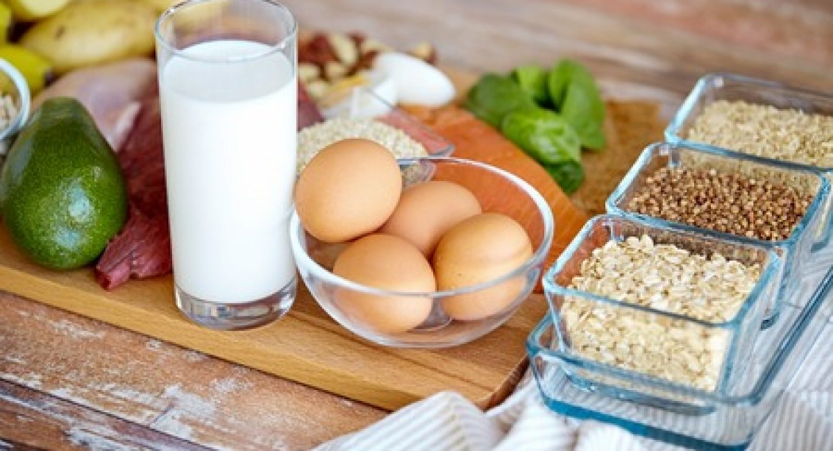 53927722 - balanced diet, cooking, culinary and food concept - close up of eggs, cereals and milk glass on wooden table